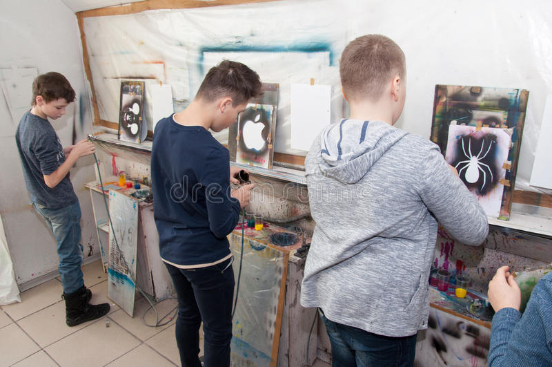 O grupo de pintura dos adolescentes das crianças com um aerógrafo coloriu brilhantemente imagens em um estúdio artístico - Rússia foto de stock