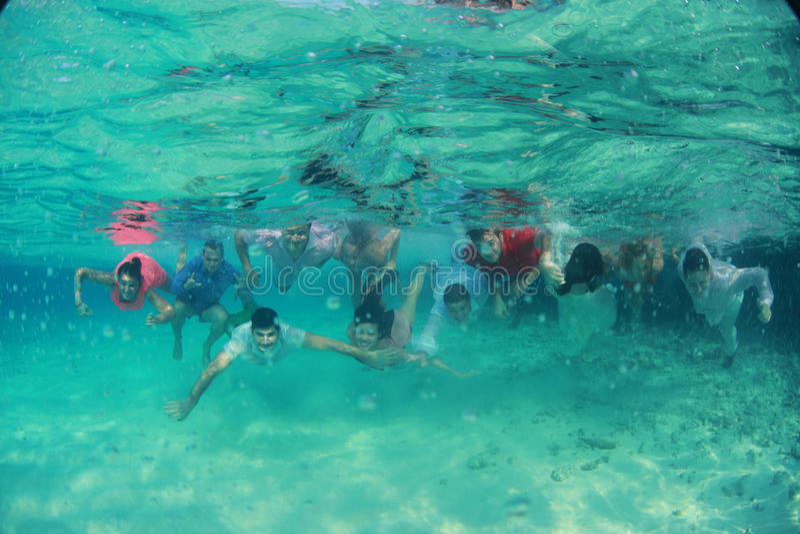 O grupo de povos felizes novos dos amigos nada mergulhando debaixo d'água com os noivos nupciais dos pares perto deles o casament fotografia de stock