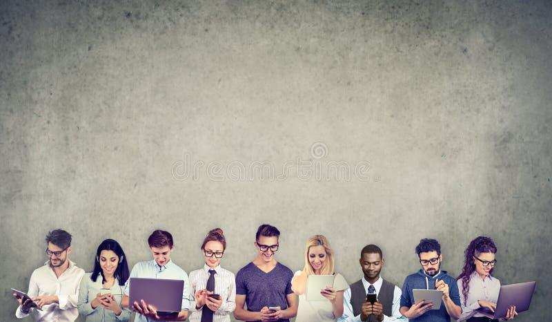 O grupo de povos multiculturais conectou usando dispositivos móveis digitais imagem de stock