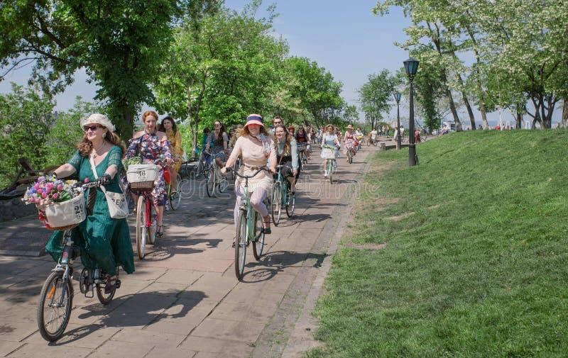 O grupo de sêniores e as jovens mulheres na forma velha denominam o ciclismo com a bicicleta do vintage no cruzeiro retro do fest fotos de stock