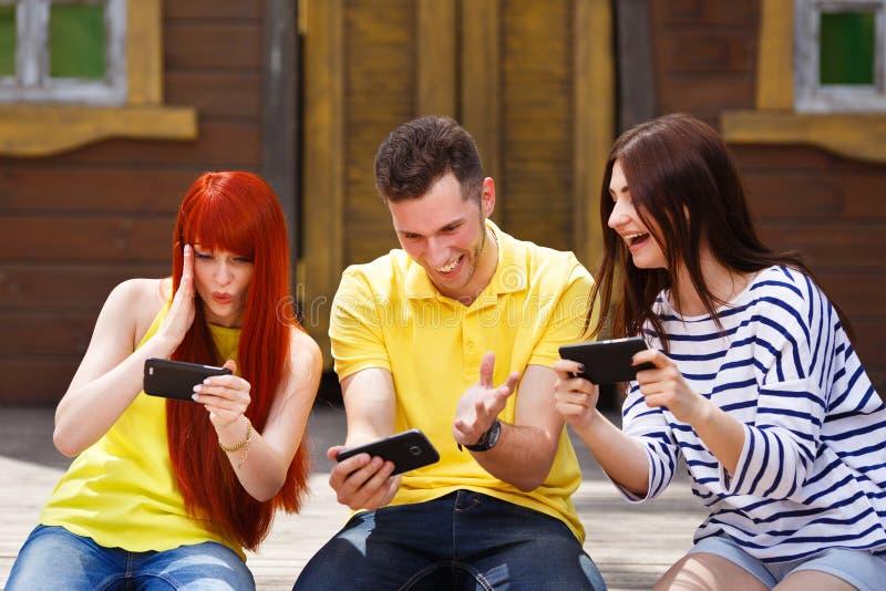 O grupo de três amigos joga o jogo de vídeo móvel fora, a menina e foto de stock royalty free