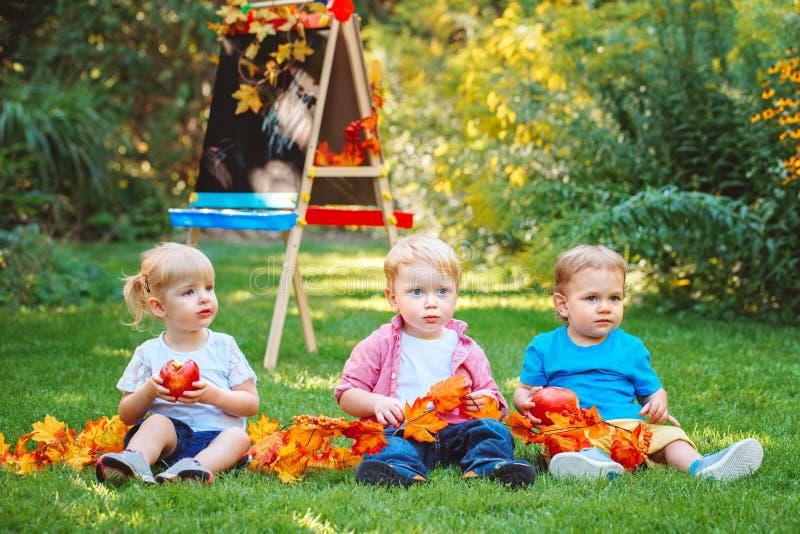 O grupo de três crianças caucasianos brancas da criança caçoa os meninos e a menina que sentam-se fora no parque do outono do ver imagens de stock