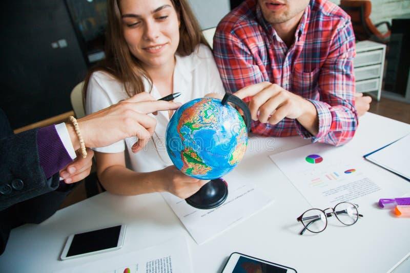 O grupo de três jovens com globo escolhe o país viajar a foto de stock