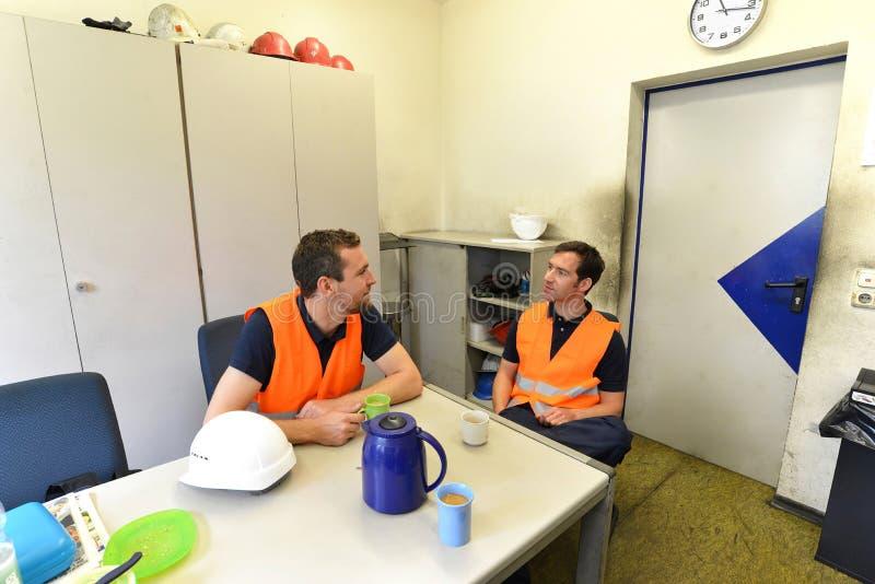 O grupo de trabalhadores em uma empresa industrial toma uma ruptura de café imagens de stock royalty free