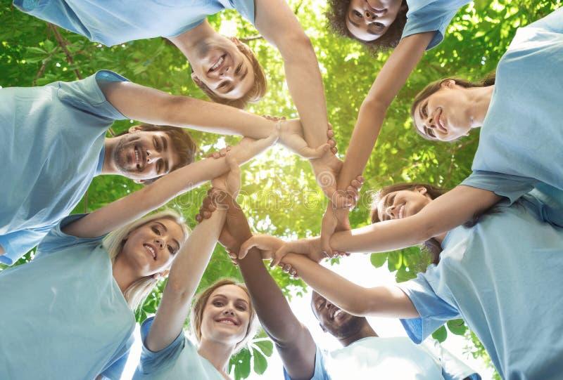 O grupo de voluntários felizes colabora no parque imagens de stock royalty free