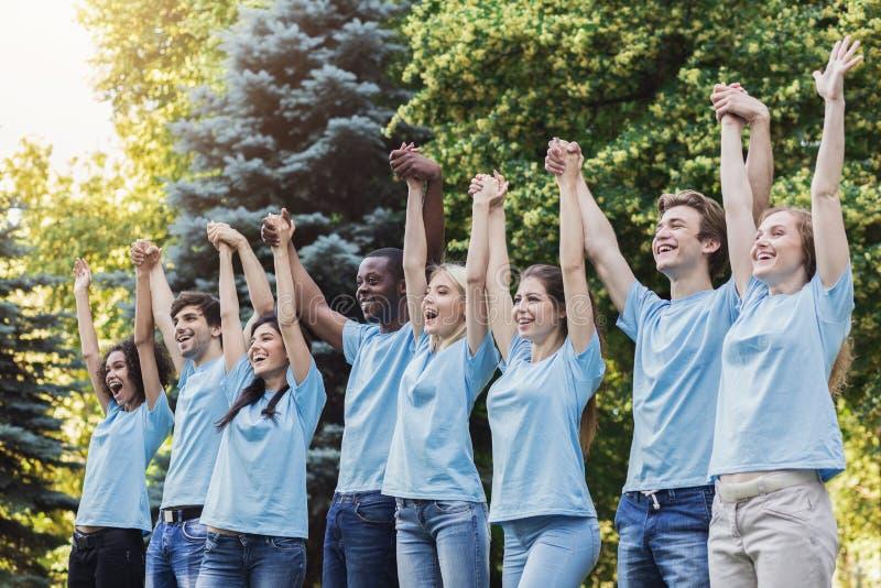 O grupo de voluntários novos junta-se às mãos no parque fotos de stock royalty free