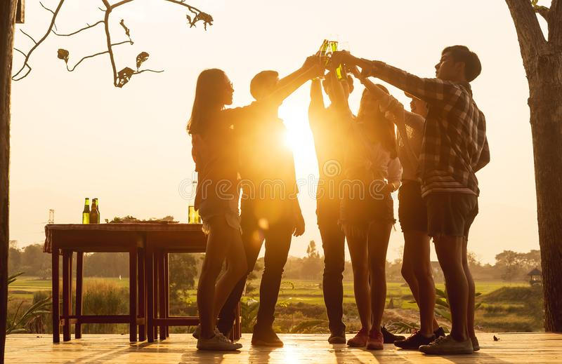 O grupo do adolescente 6 tem o partido de jantar que comemora em toas do por do sol imagens de stock