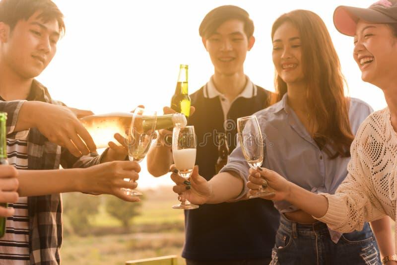 O grupo do adolescente 6 tem o partido de jantar que comemora no por do sol para derramar fotografia de stock royalty free