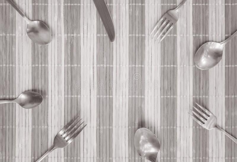 O grupo do close up de colher e de faca inoxidáveis da forquilha na esteira de madeira textured o fundo com espaço da cópia no ce foto de stock royalty free