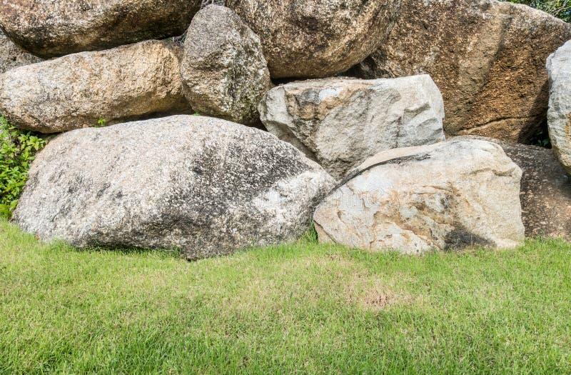 O grupo do close up de rocha grande para decora com grama verde no fundo da textura do jardim fotografia de stock