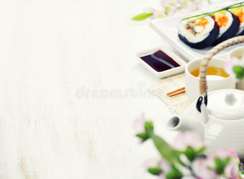 O grupo do sushi, o chá verde e sakura ramificam fotografia de stock royalty free