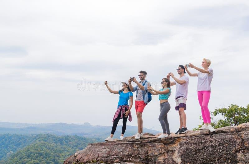 O grupo do turista com trouxa toma a foto da paisagem da parte superior da montanha no telefone de Smart da pilha foto de stock royalty free