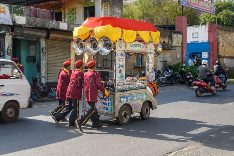 O grupo dos artistas masculinos está empurrando o carro da música na rua em Ajmer India imagem de stock