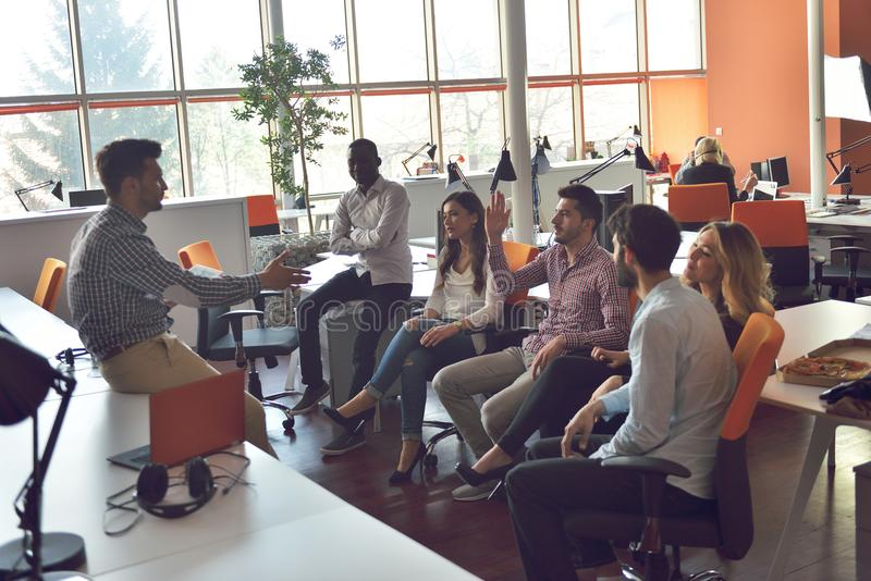 O grupo dos jovens no escritório moderno tem a reunião e a sessão de reflexão da equipe ao trabalhar no portátil e no café bebend fotografia de stock