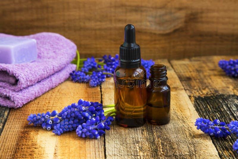 O grupo dos termas com as garrafas de óleos da aromaterapia e as flores roxas cortejam sobre imagem de stock royalty free