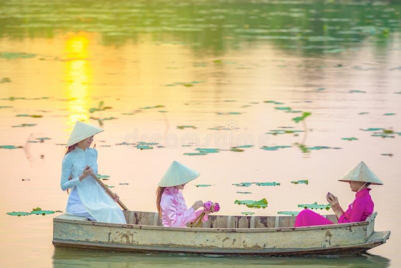O grupo fêmea vietnamiano em mulheres asiáticas de um barco de madeira dos lótus senta-se em um barco de madeira para recolher fl fotos de stock