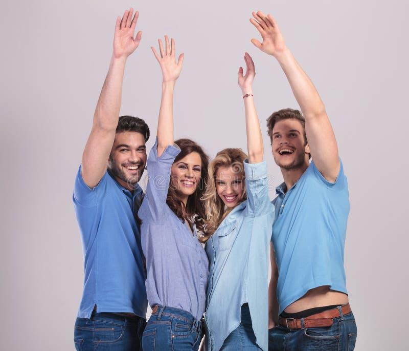 O grupo feliz de jovens que comemoram o sucesso com mãos aumenta foto de stock