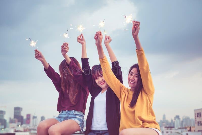 O grupo feliz de namoradas de Ásia aprecia e joga o chuveirinho no telhado fotografia de stock
