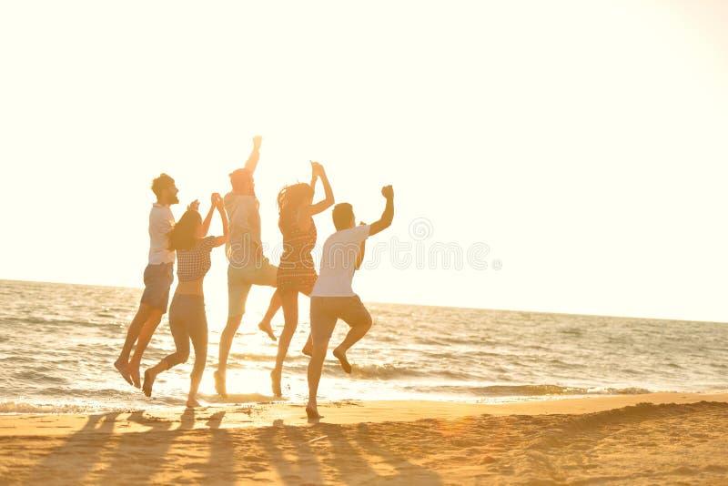 O grupo feliz dos jovens tem o corredor branco do divertimento e o salto no beacz no tempo do por do sol imagens de stock