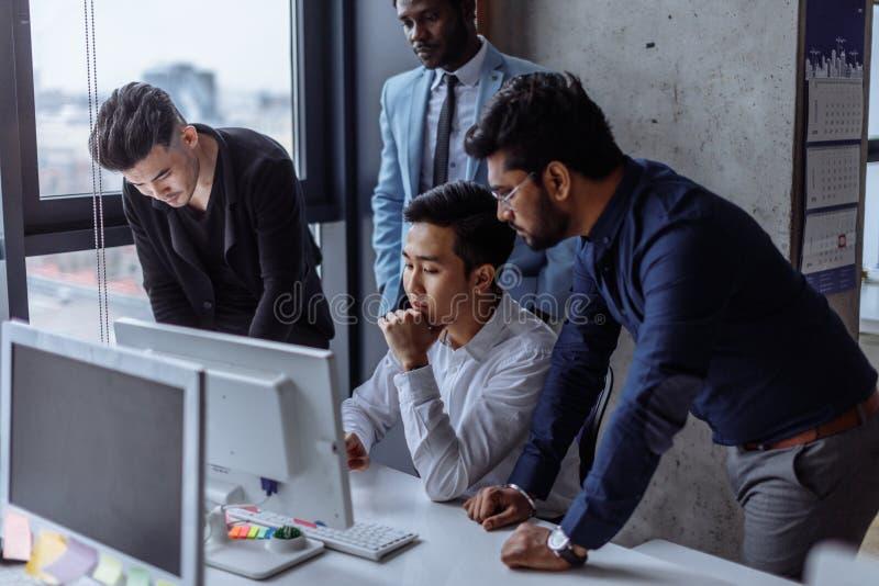 O grupo focalizou os executivos masculinos recolhidos em torno do computador na fala do escritório fotos de stock