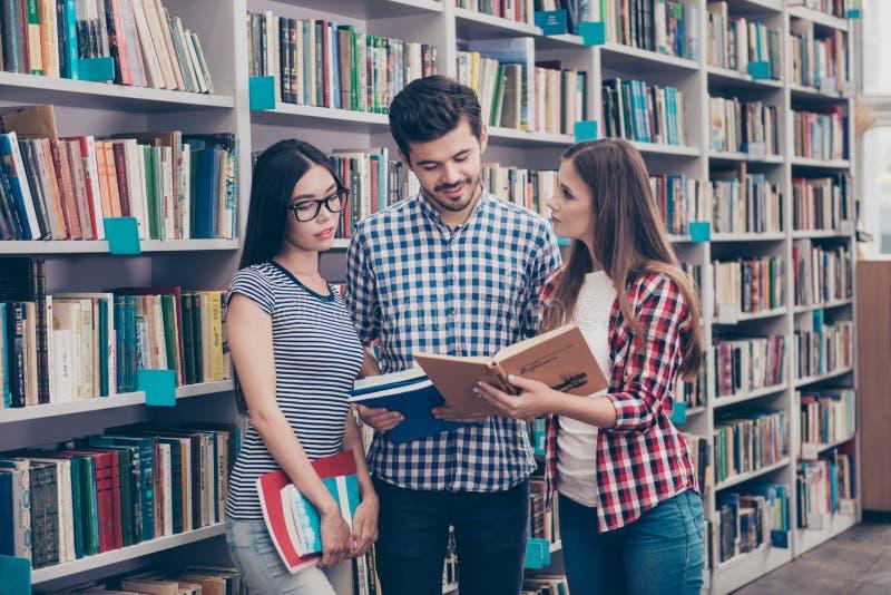 O grupo internacional de três focalizou o bookw novo inteligente dos estudantes fotos de stock