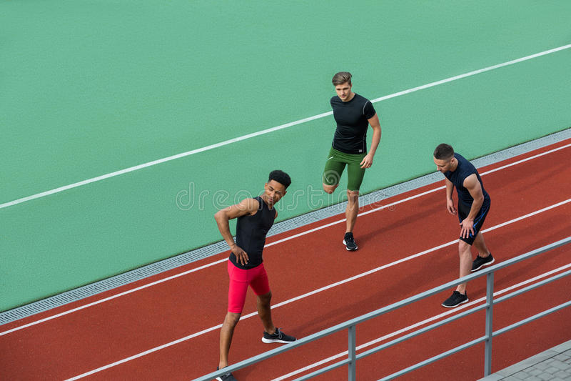 O grupo multi-étnico novo do atleta faz o esticão de exercícios foto de stock royalty free