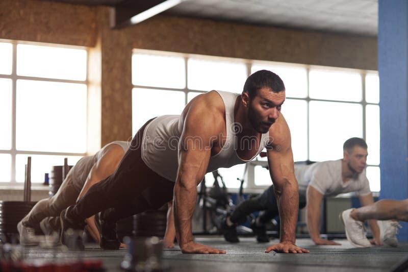 O grupo pequeno de adultos masculinos musculares que aquecem o impulso do treinamento levanta foto de stock royalty free