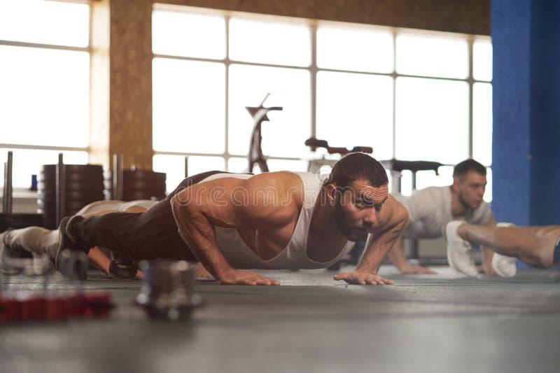 O grupo pequeno de adultos masculinos musculares que aquecem o impulso do treinamento levanta imagens de stock