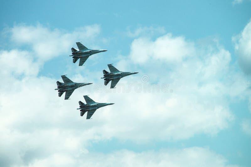 O grupo quatro do avião militar dos lutadores, avião do jato no céu faz manobras fotografia de stock royalty free