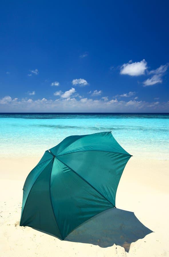 O guarda-chuva está em uma praia imagens de stock