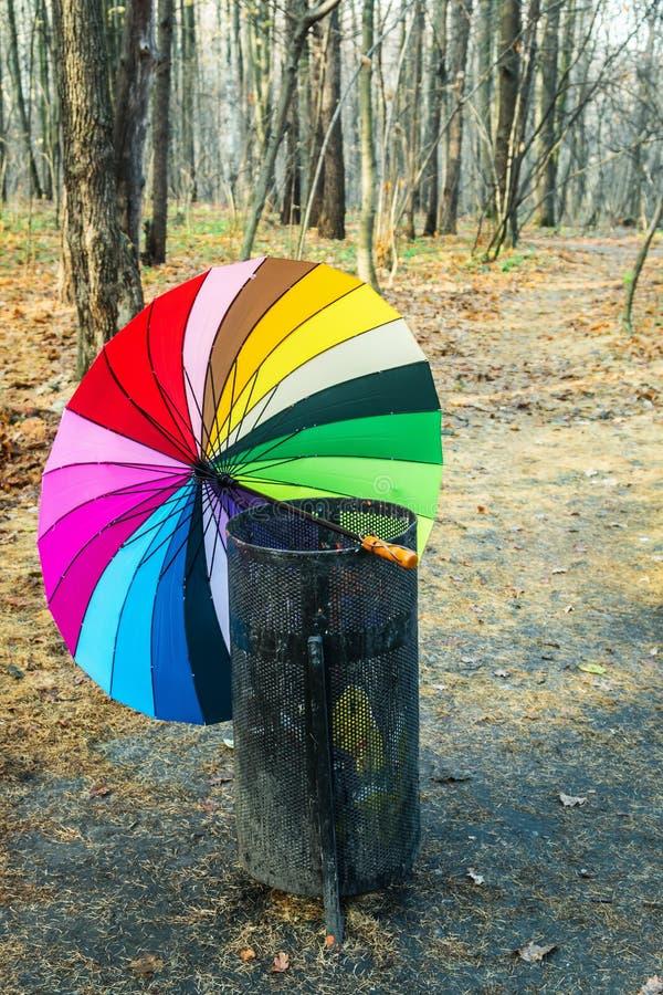 O guarda-chuva multi-colorido Opened descansa em um lixo imagens de stock royalty free