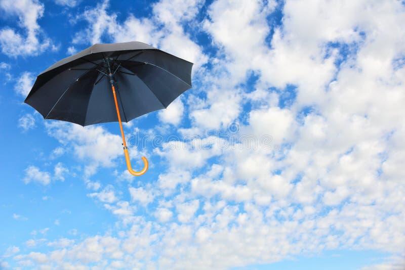 O guarda-chuva preto voa no céu contra de nuvens brancas puras Mary Po fotografia de stock