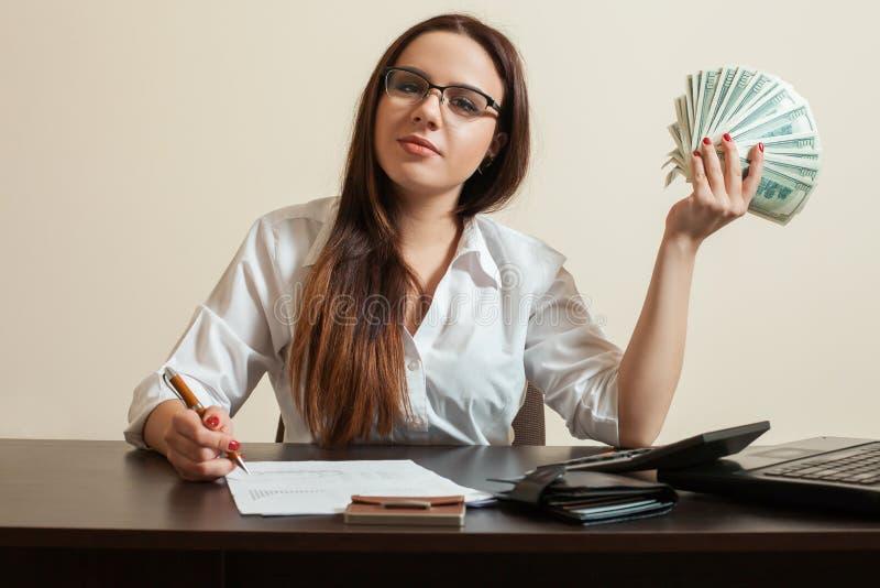 O guarda-livros fêmea que guarda dólares ventila em sua mão foto de stock royalty free