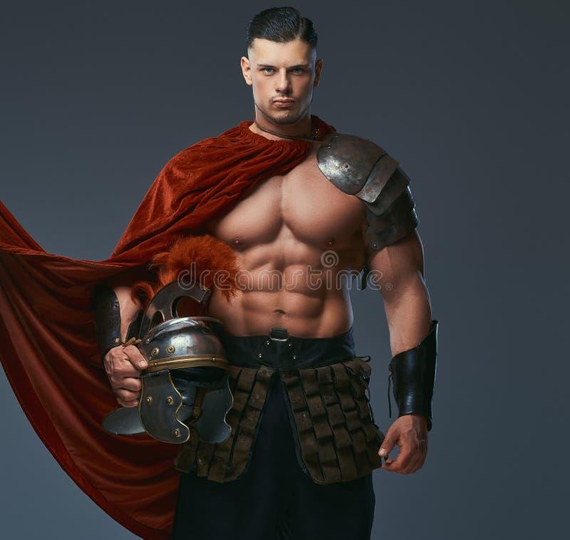 O guerreiro brutal de Grécia antigo com um corpo muscular em uniformes da batalha guarda um capacete ao estar em um estúdio imagens de stock
