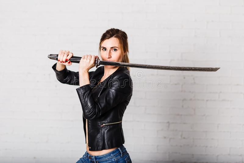 O guerreiro da mulher em um casaco de cabedal preto com uma espada pesada em suas mãos imagem de stock