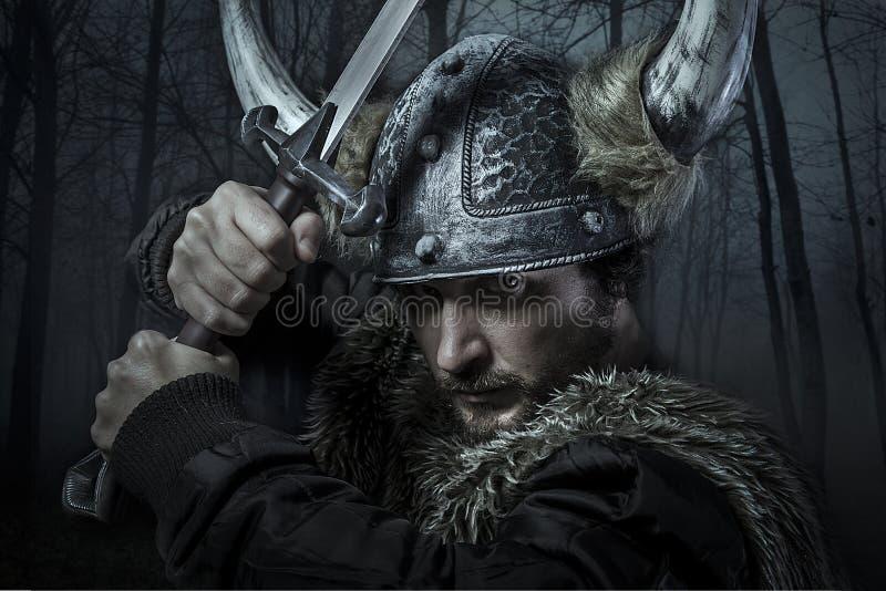O guerreiro de Viking, homem vestiu-se no estilo bárbaro com espada, urso foto de stock