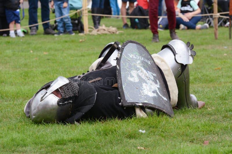 O guerreiro medieval na armadura encontra-se na terra na derrota imagens de stock