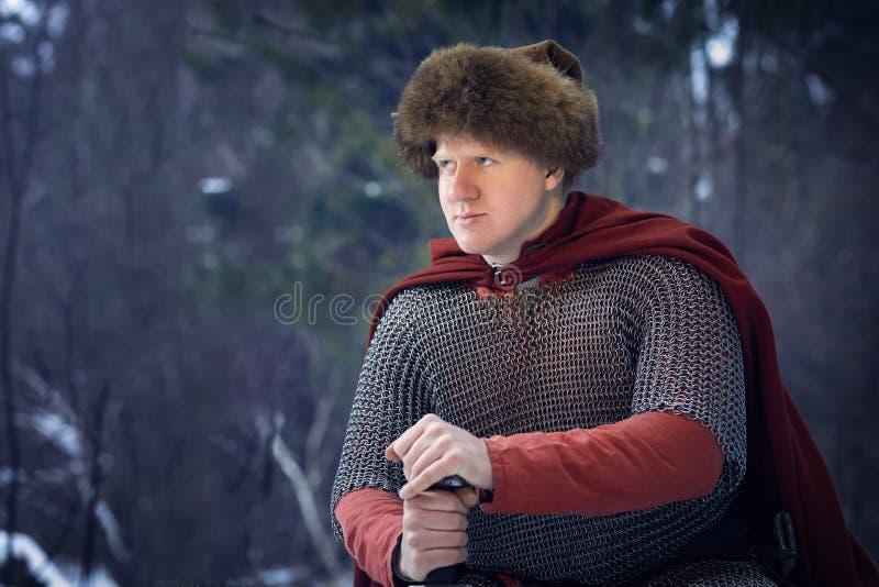 O guerreiro medieval no cloack vermelho guarda a espada imagens de stock royalty free