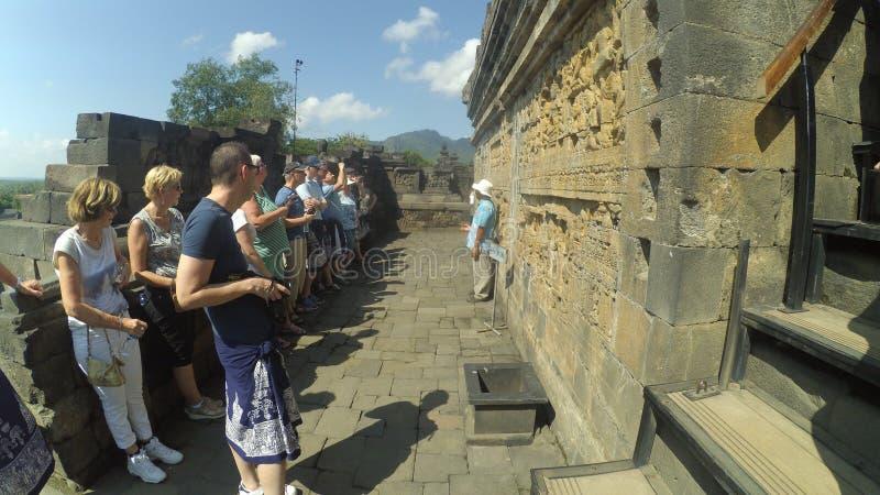 O guia explica a história do templo de Borobudur aos turistas, em Muntilan, Java central fotografia de stock
