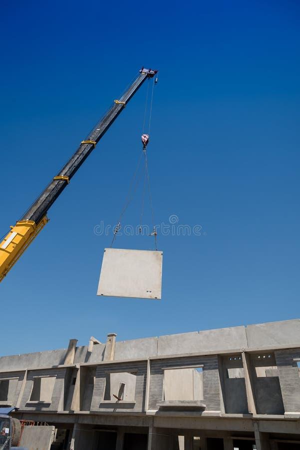 O guindaste do canteiro de obras está levantando um painel de muro de cimento pré-fabricado foto de stock royalty free