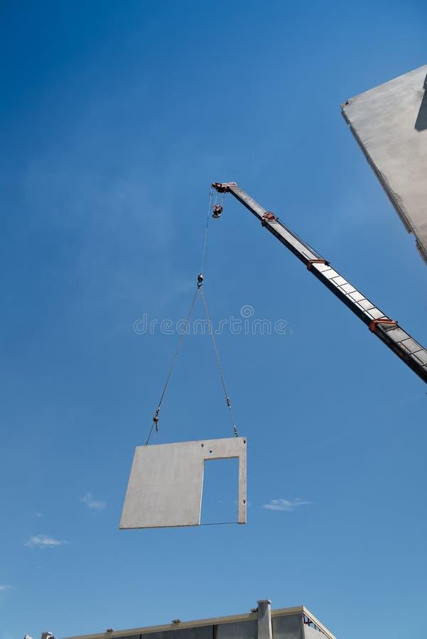 O guindaste do canteiro de obras está levantando um painel de muro de cimento pré-fabricado imagens de stock royalty free