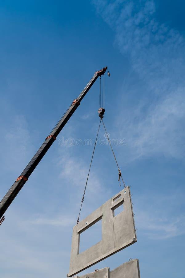 O guindaste do canteiro de obras está levantando um painel de muro de cimento pré-fabricado fotografia de stock royalty free