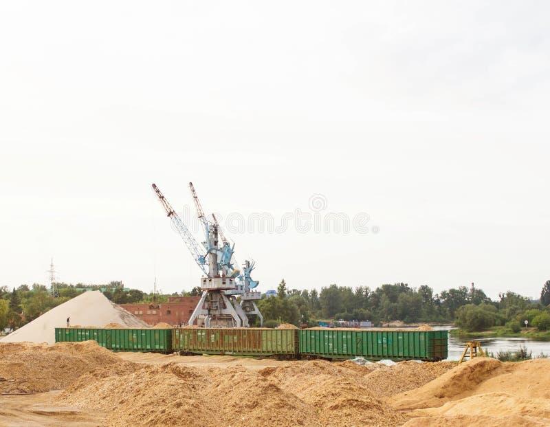 O guindaste do porto faz a carga das microplaquetas de madeira nos carros de frete do trem, carga imagem de stock