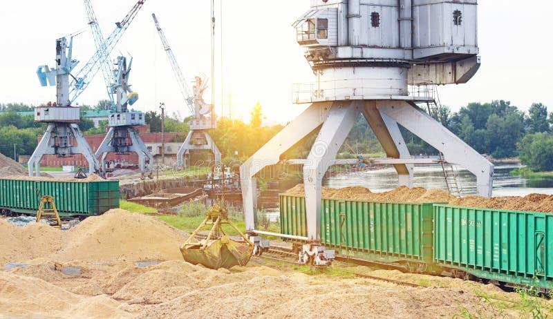 O guindaste do porto faz a carga das microplaquetas de madeira nos carros de frete do trem, carga, o sol fotos de stock