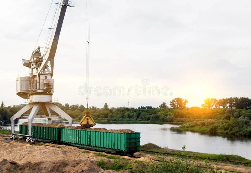 O guindaste do porto faz a carga das microplaquetas de madeira nos carros de frete do trem, carga, o sol foto de stock royalty free