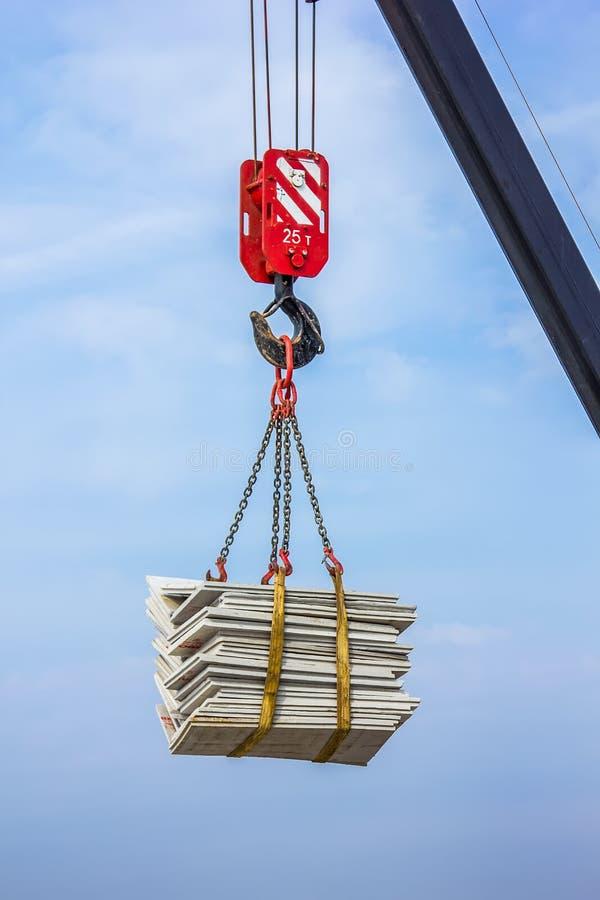 O guindaste levanta uma carga pesada em um gancho foto de stock