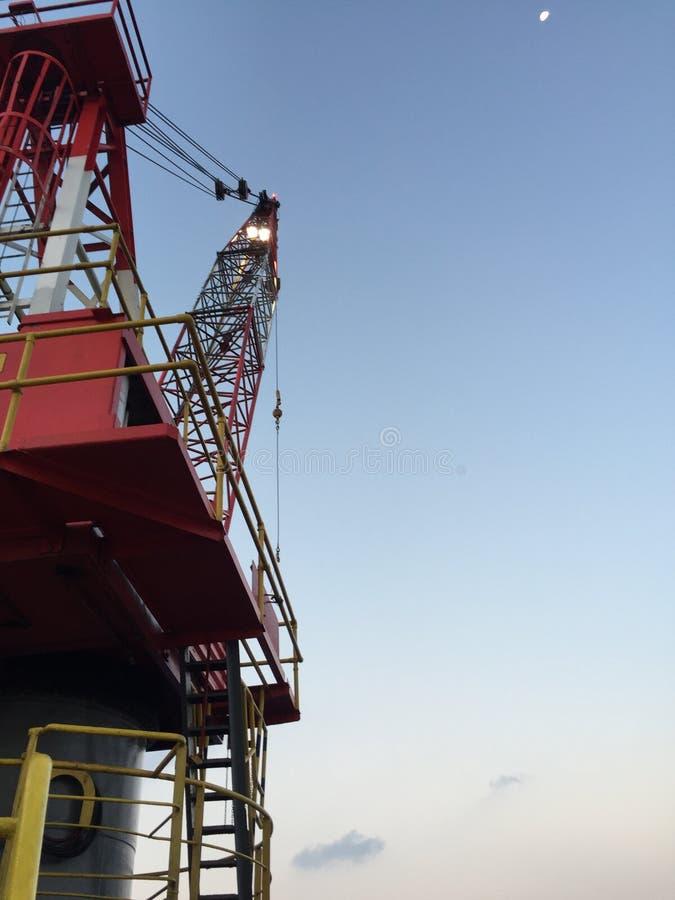 O guindaste no pé do lado de porto na pouca distância do mar levanta acima o equipamento foto de stock