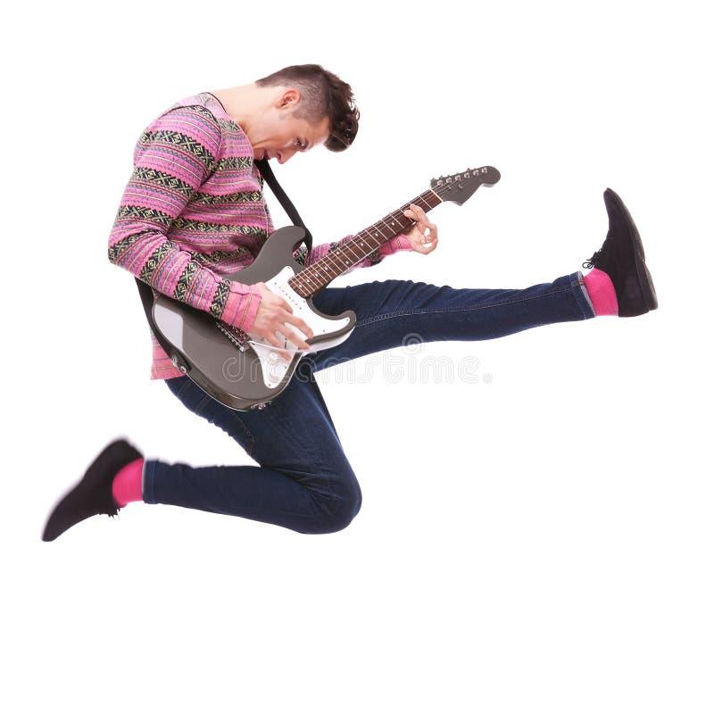 O guitarrista apaixonado salta no ar fotografia de stock