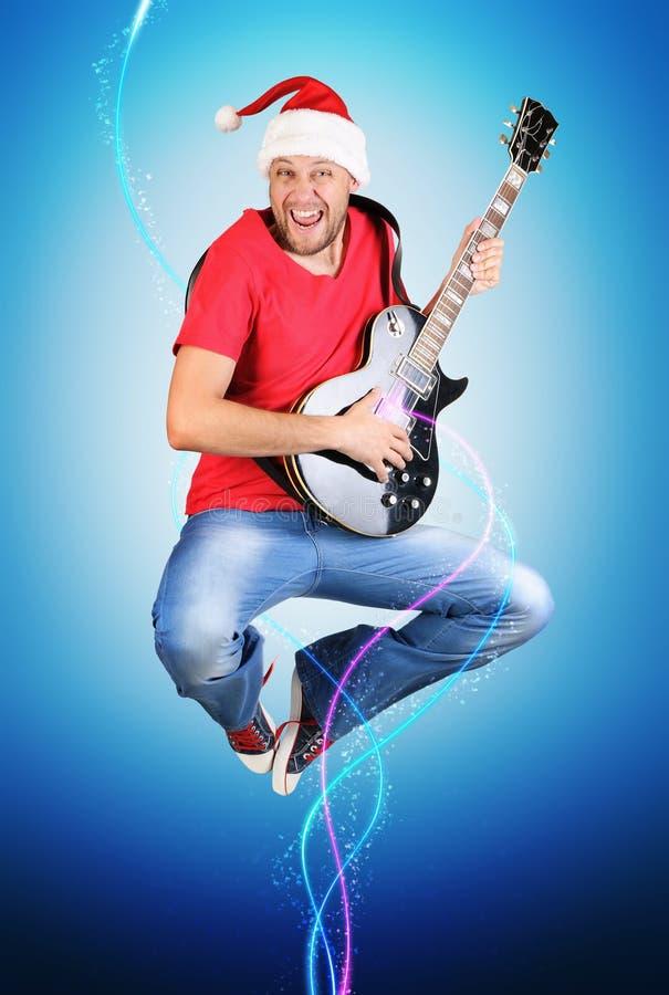 O guitarrista estilizado de Papai Noel salta, conceito fotografia de stock royalty free