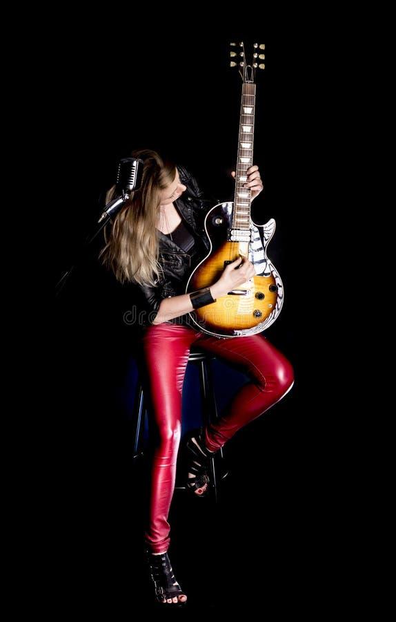 O guitarrista louro profissional, à moda da menina joga pela guitarra elétrica no casaco de cabedal Mostras do professor da mulhe imagem de stock royalty free
